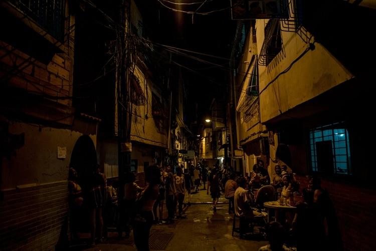Los vecinos de un barrio de la clase trabajadora esperaban en las calles el restablecimiento del servicio eléctrico. No tuvieron agua potable durante dieciséis días y, durante 72 horas, tampoco hubo electricidad en la zona. (Meridith Kohut para The New York Times)