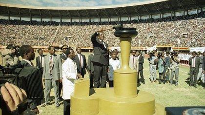 Mugabe enciende una llama para celebrar el décimo aniversario de la independencia de la nación, en el National Sports Center de Harare el 18 de abril de 1990
