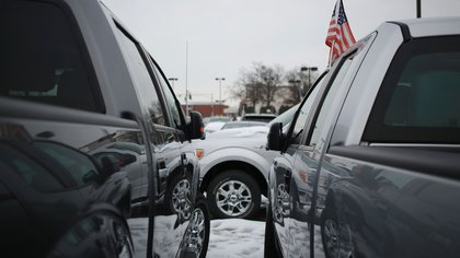An U.S. flag is seen on a 2014 Ford Motor Co. F-150 truck displayed for sale at the Oxmoor Ford car dealership in Louisville, Kentucky, U.S., on Wednesday, Feb. 25, 2015. Domestic and total vehicle sales figures are scheduled to be released on March 3. Photographer: Luke Sharrett/Bloomberg