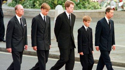 En esta foto de archivo tomada el 6 de septiembre de 1997 durante el funeral de Lady Di (Diana Spencer) los asistentes de la Familia Real no vistieron sus uniformes por varios motivos: el principal, la madre de los príncipes ya no formaba parte de la Casa Real y sus hijos aún no habían actuado militarmente. De izquierda a derecha: el príncipe Felipe, duque de Edimburgo, el príncipe Harry, el conde Spencer, el príncipe Harry y el príncipe Carlos de Gales, caminan frente a la abadía de Westminster durante el funeral (AFP)