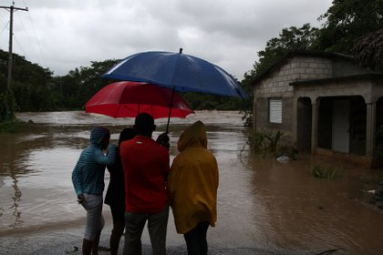 Un grupo de personas observa el río Soco tras el paso del huracán María en El Seibo, República Dominicana (Reuters)