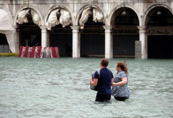Una pareja pasea por la inundada plaza San Marco (REUTERS/Manuel Silvestri)