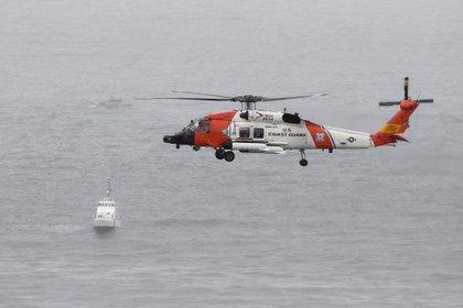 Un helicóptero de la Guardia Costera de los EEUU sobrevuela a los barcos que buscan en el área donde un barco volcó cerca de la costa de San Diego el domingo. (AP Photo/Denis Poroy)