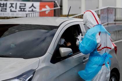 Foto de archivo de un trabajador de salud, usando un traje de protección, controla a un visitante a la entrada del Yeungnam University Medical Center en Daegu, Corea del Sur, en medio de la pandemia de coronavirus. Mar 3, 2020. REUTERS/Kim Kyung-Hoon