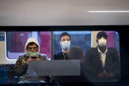 Pasajeros con barbijos en la metropolitana de Londres (Victoria Jones/PA Wire/dpa)
