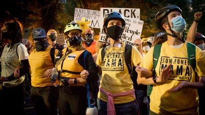 """""""Wall of Moms"""". En el marco de las protestas por la desigualdad racial y el asesinato de George Floyd, en Portland, cientos de madres, vestidas de amarillo, construyeron un muro humano entre manifestantes y oficiales federales, mientras cantaban: «Manos arriba, por favor no disparen», en versión canción de cuna."""