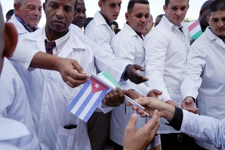 Médicos cubanos reciben banderas cubanas e italianas durante una ceremonia de despedida antes de partir a Italia para ayudar con la propagación del brote de la enfermedad por coronavirus (COVID-19), en La Habana, Cuba. 21 de marzo de 2020. REUTERS/Alexandre Meneghini