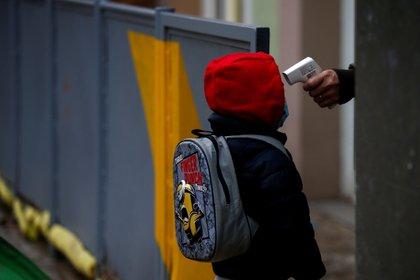 Una profesora toma la temperatura a un alumno, en una escuela de España (Foto: EFE)