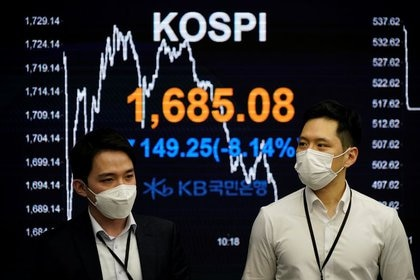 FILE PHOTO.  Stock traders walk past an electronic dashboard displaying the Korean Stock Price Index (KOSPI) in a bank trading room in Seoul, South Korea.  March 13, 2020. REUTERS / Kim Hong-ji