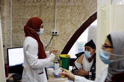 Un trabajador médico se prepara para vacunar a un hombre contra la enfermedad del coronavirus mientras Israel continúa su campaña nacional de vacunación (Reuters)