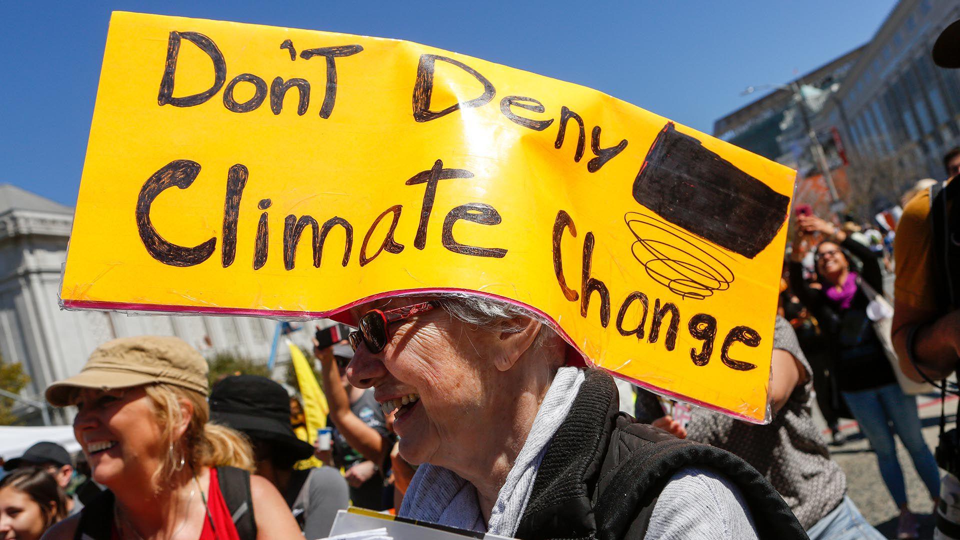 """""""No neguemos el cambio climático"""", dice la particular pancarta de este hombre protestando contra las medidas de Trump frente a la Casa Blanca en 2018. (AFP)"""