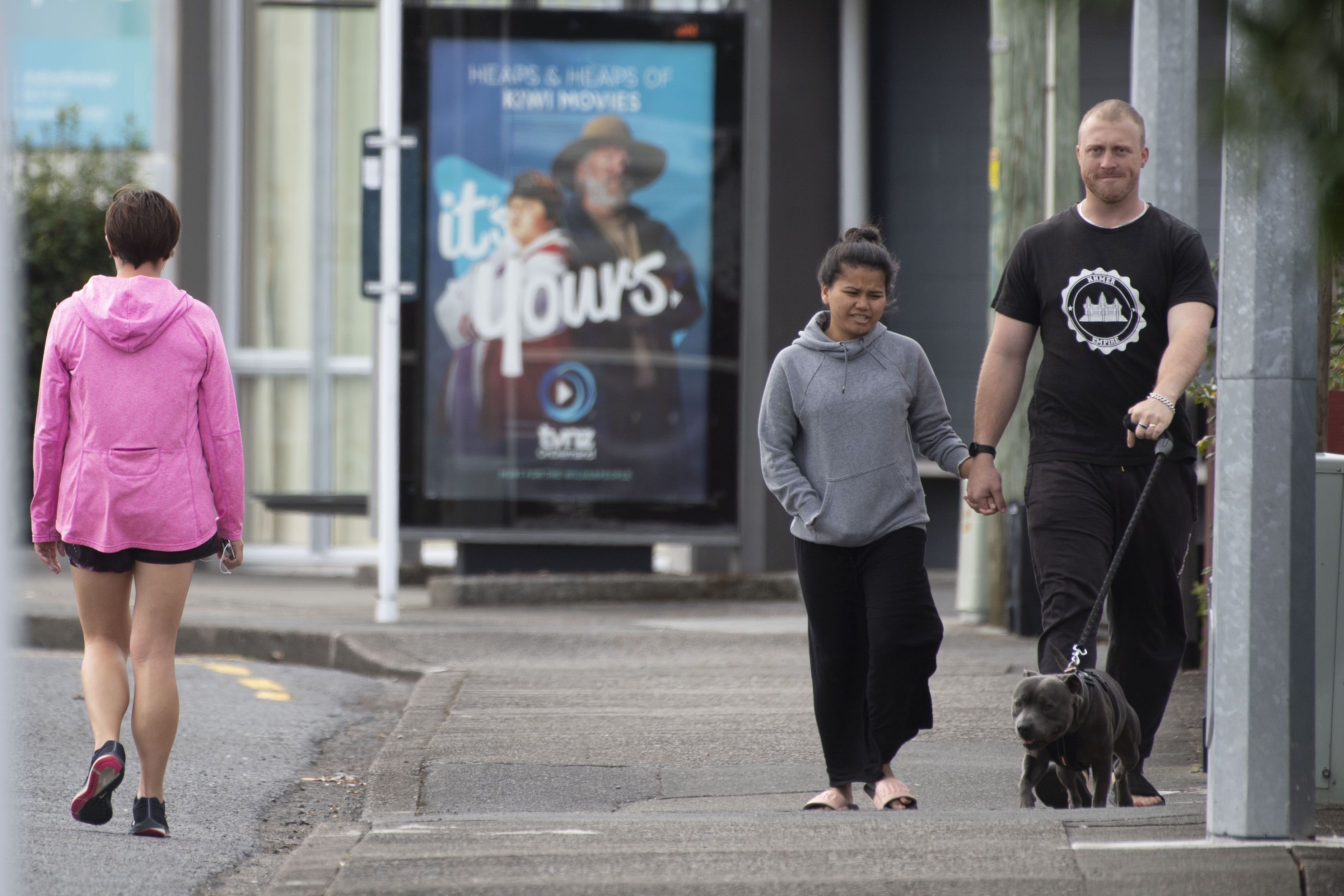 Pedestrians practise social distancing in response to the COVID-19 coronavirus outbreak along a street of Lower Hutt, near Wellington, on April 20, 2020. - New Zealand will ease a nationwide COVID-19 lockdown next week after claiming success in stopping