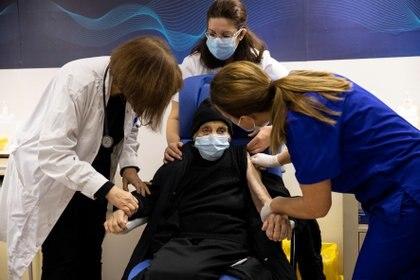 Personal médico conversa con una anciana que recibió una vacuna en Grecia (Reuters)