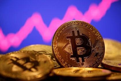 Una representación de la moneda virtual Bitcoin se ve delante de un gráfico de acciones en esta ilustración tomada el 8 de enero de 2021 (REUTERS/Dado Ruvic/File Photo)