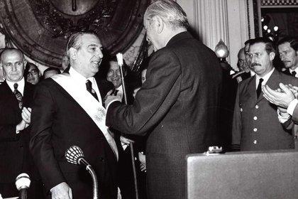 Hector Cámpora entre el bastón presidencial a Raúl Lastir. A la izquierda Llambí observa conseriedad, en el medio José Ber Gelbard sonríe