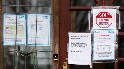 """Un cartel de """"No ingresar"""" y con información del Servicio Nacional de Salud (NHS) sobre el coronavirus en la entrada de una cirugía de médicos en el norte de Londres (REUTERS / John Sibley)"""