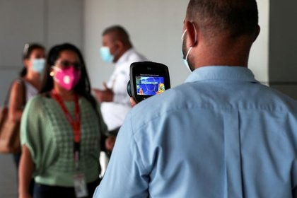 FILE PHOTO: An employee measures the temperatures of travelers at the Tocumen International Airport during the coronavirus disease (COVID-19) outbreak, in Panama City, Panama October 16, 2020. Picture taken October 16, 2020. REUTERS/Erick Marciscano/File Photo