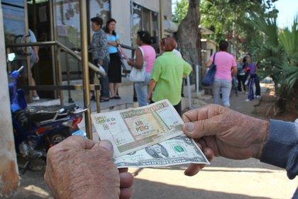 Un hombre muestra un peso convertible cubano y un dólar estadounidense