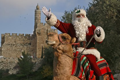 Issa Kassissieh, más conocido como el Papá Noel de Jerusalén, monta un camello fuera de los muros de la Ciudad Vieja de Jerusalén (Foto de MENAHEM KAHANA / AFP)
