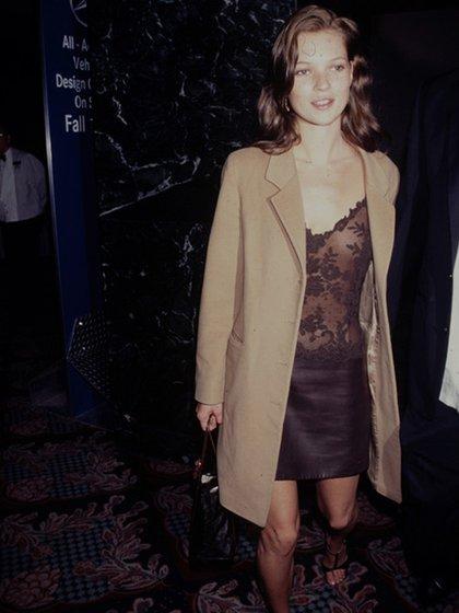 Kate Mossbrilló en los 90 como ninguna otra modelo lo iba a poder lograr. De minifalda y top lencero, un sobretodo camel y sandalias negras (Getty Images)