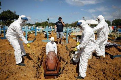 Alexandro Pinheiro Martins, de 32 años, reacciona durante el entierro de su hermana Elissandra Pinheiro, de 39, y su sobrina Maria Ketheleen, 22, que fallecieron debido a la enfermedad del coronavirus COVID-19, en el cementerio Parque Taruma en Manaus, Brasil, 17 de enero de 2021. REUTERS/Bruno Kelly