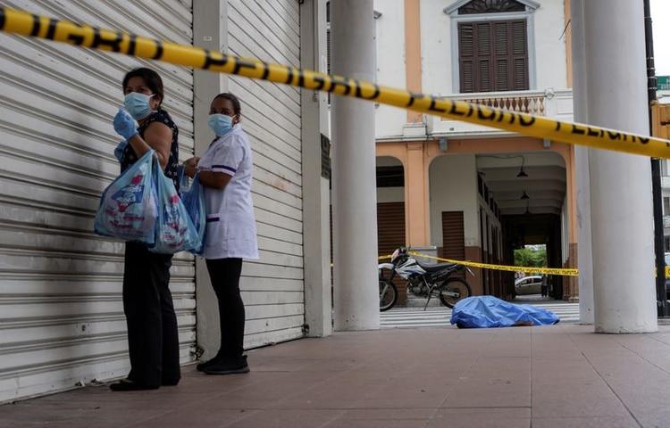 Dos mujeres con mascarillas pasan junto al cadáver de un hombre que se desplomó al suelo en Guayaquil, Ecuador (REUTERS/Vicente Gaibor del Pino)