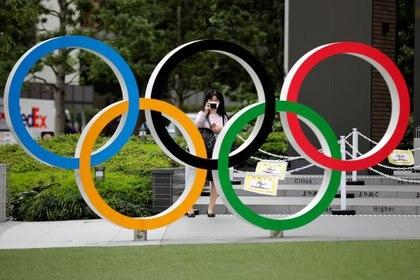 Una mujer utilizando mascarilla toma una fotografía a os anillos olímpicos frente al Estadio Nacional de Tokio, Japón October 14, 2020. REUTERS/Kim Kyung-Hoon