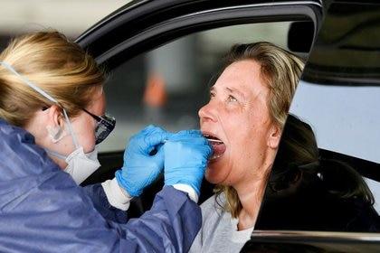 Un miembro del personal médico toma muestras de prueba de coronavirus de una mujer durante la prueba de enfermedad por coronavirus (COVID-19) en una pista de hielo convertida, en Alkmaar, Países Bajos (REUTERS/Piroschka van de Wouw/File Photo)
