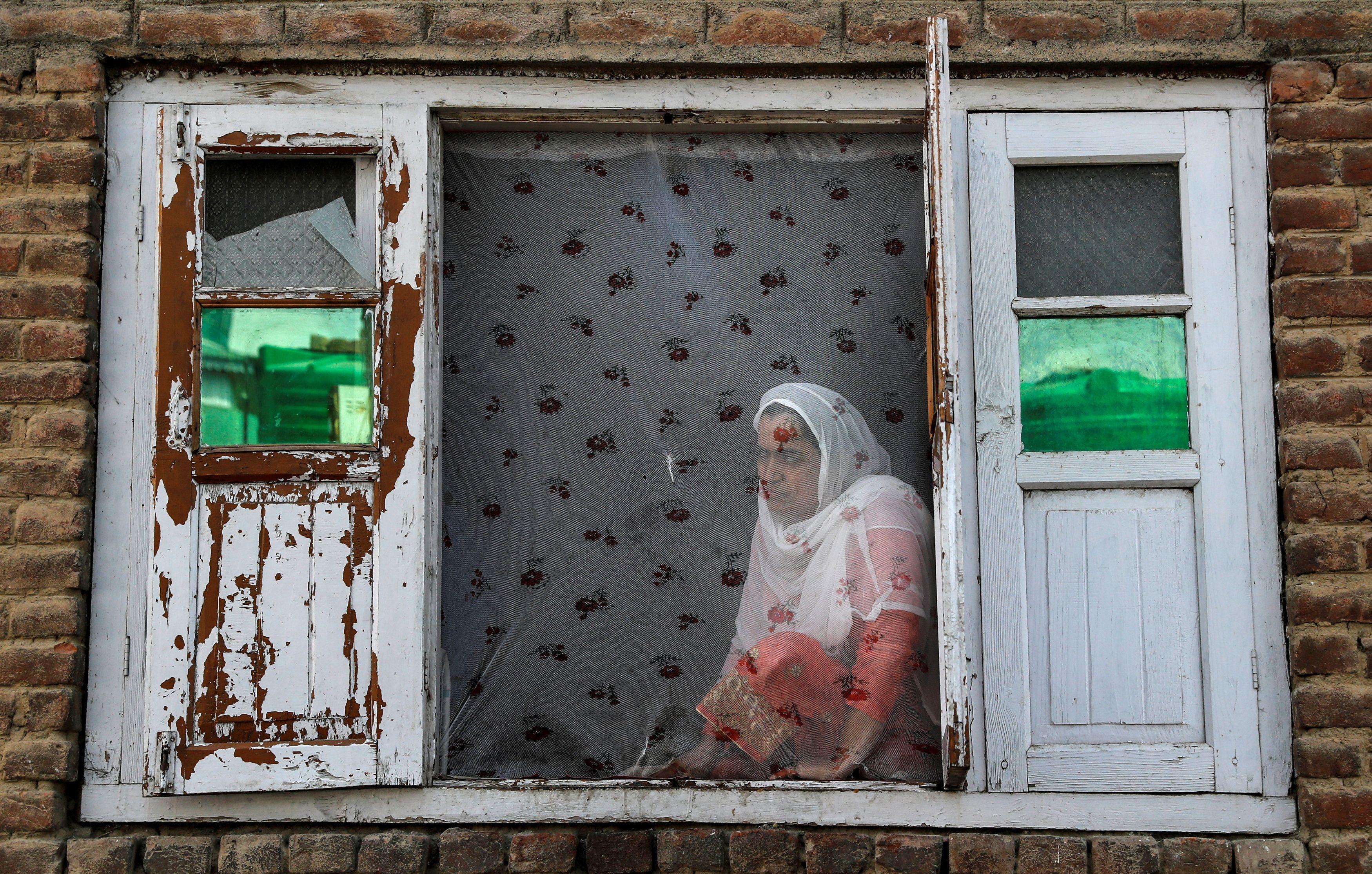 Una mujer de Cachemira observa las protestas en el barrio de Anchar después de las oraciones del viernes, durante las restricciones tras la eliminación del estatus constitucional especial para Cachemira por parte del gobierno indio, en Srinagar el 20 de septiembre de 2019.