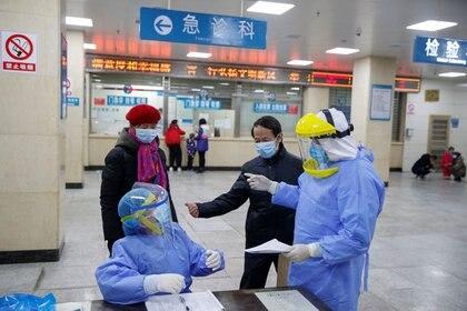 Enfermeras con equipo de protección hablan con las personas en la recepción del First People's Hospital, en Yueyang, provincia de Hunan.   (REUTERS/Thomas Peter)