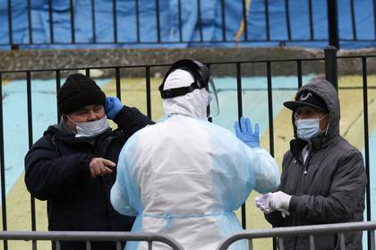 Un trabajador distribuye equipos de protección personal a las personas que esperan en la fila para ser examinados (REUTERS/Stefan Jeremiah)