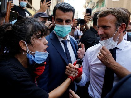 French President Emmanuel Macron listens to a resident as he visits a devastated street of Beirut, Lebanon August 6, 2020. Thibault Camus/Pool via REUTERS