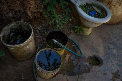Se observan envases plásticos donde se almacena agua que emana de piedras en una barriada, en Caracas (EFE/ Miguel Gutiérrez)