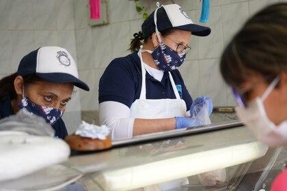 Una mujer compra pescado en una tienda en Montevideo el 10 de abril de 2020. (REUTERS/Mariana Greif)