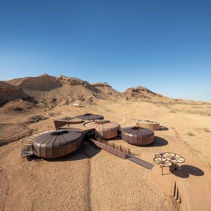 El Centro de Interpretación del Parque Geológico de Buhais se ha construido sobre un antiguo lecho marino en el desierto a 48 kilómetros al sureste de Sharjah, con edificios que se asemejan a erizos de mar fosilizados. Las cápsulas cuentan con espacios expositivos, teatros, una cafetería con impresionantes vistas a las montañas. Además de contemplar la impresionante arquitectura, los visitantes pueden ver fósiles de hace más de 65 millones de años (Hopkins Architects)