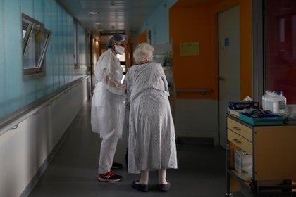 Un fisioterapeuta, con una máscara protectora y un traje de protección, acompaña a una mujer anciana en una unidad de neumología en el hospital de Vannes, donde se encuentran los pacientes que padecen la enfermedad del coronavirus, Francia [12 de octubre de 2020] (Reuters/ Stephane Mahe)