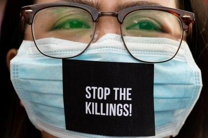 """Una mujer utiliza una máscara contra el coronavirus con el slogan """"paren las muertes"""" en Filipinas ( REUTERS/Eloisa Lopez)"""