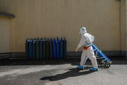 Un trabajador médico con traje protector transporta un tanque de oxígeno en el Hospital de la Cruz Roja de Wuhan en Wuhan, el epicentro del nuevo brote de coronavirus, en la provincia de Hubei, China, 16 de febrero de 2020. (China Daily vía REUTERS)