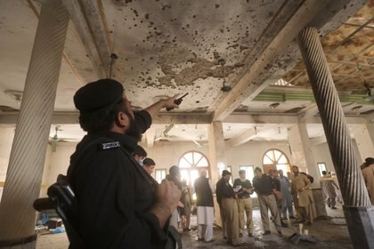 Un oficial de policía señala el techo dañado mientras otros inspeccionan el lugar de la explosión de una bomba en un seminario religioso en Peshawar, Pakistán. REUTERS/Fayaz Aziz