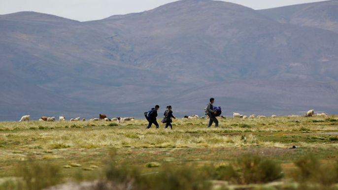 Migrantes venezolanos caminan por un sendero después de usar un cruce ilegal en la frontera con Bolivia, en Colchane, Chile.