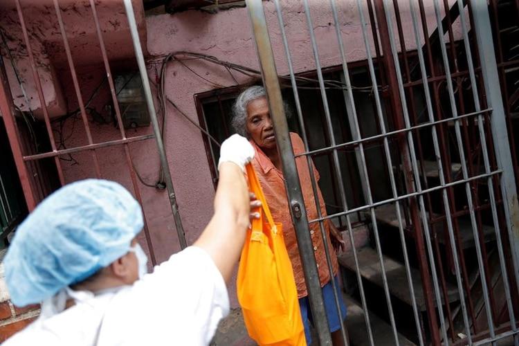 Andrea Guerrero, de 80 años, recibe una bolsa con comida en su casa de parte de una funcionaria de la municipalidad de Chacao, durante una cuarentena nacional debido al brote de un nuevo coronavirus (COVID-19), en Caracas, Venezuela. 24 de marzo de 2020. REUTERS/Manaure Quintero.