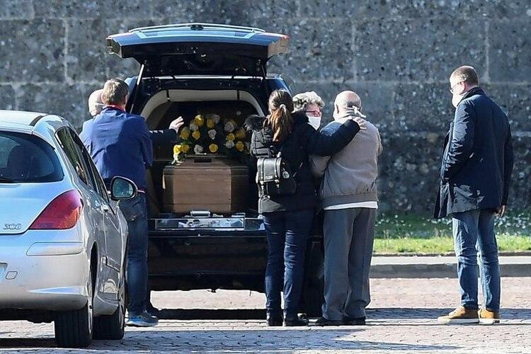 Familiares de una persona que murió por coronavirus llegan a un cementerio en Bérgamo para su sepelio