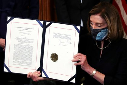 Speaker of the US House of Representatives Nancy Pelosi displays the article of impeachment against US President Donald Trump after signing it at an engrossed ceremony at the US Capitol (Reuters)