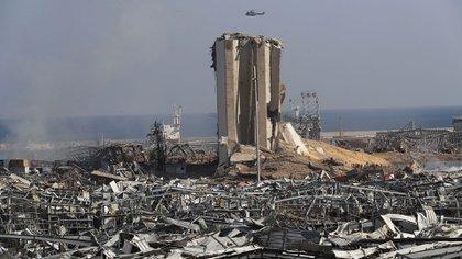 """Un helicóptero del ejército libanés sobrevuela las ruinas del puerto de Beirut donde ocurrió una gran explosión. El primer ministro Hassan Diab, en un breve discurso televisado, hizo un llamamiento a todos los países y amigos del Líbano para que brinden ayuda. a la pequeña nación, diciendo: """"Estamos presenciando una verdadera catástrofe"""". (Foto AP / Hussein Malla)"""