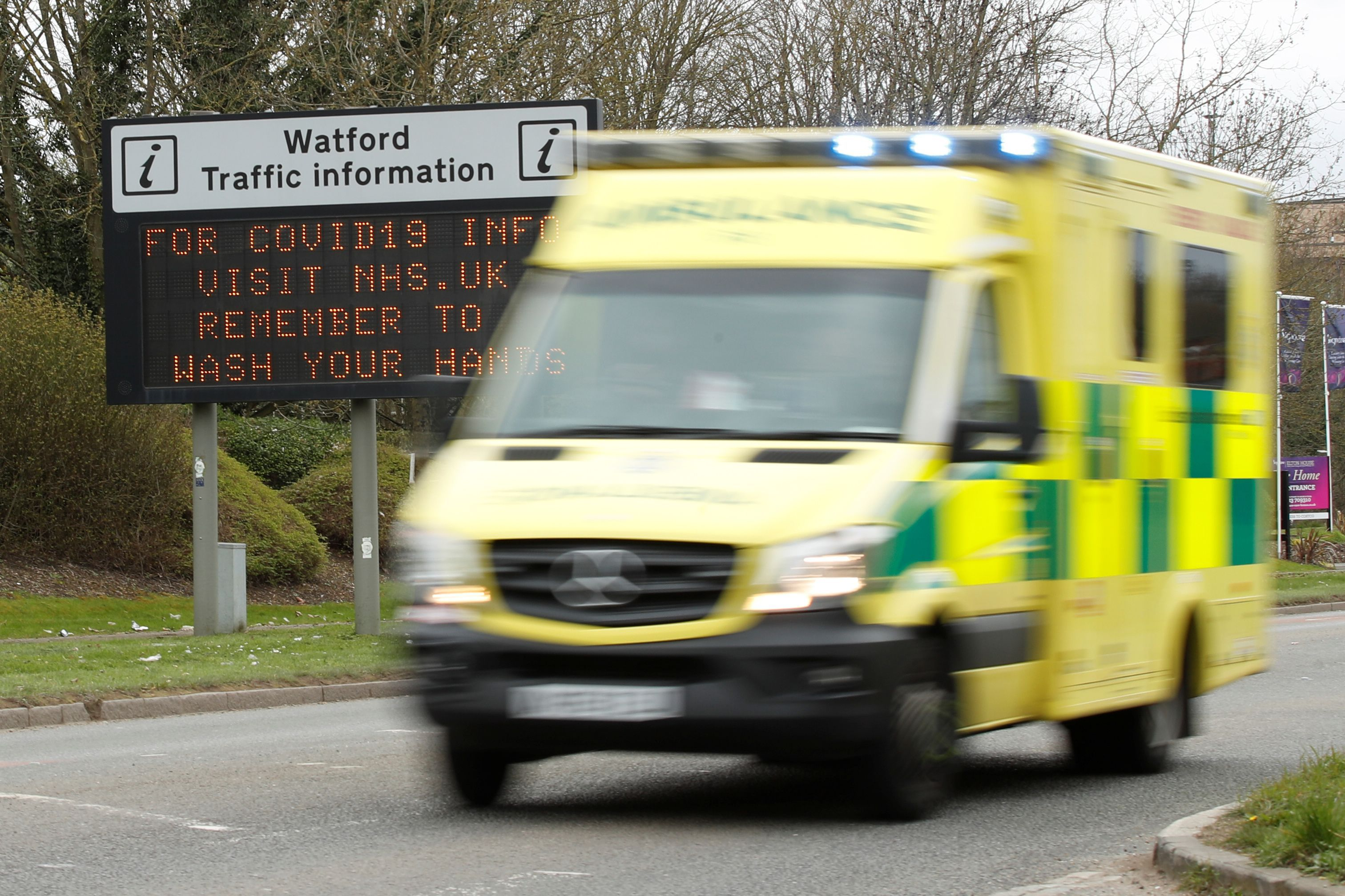 General view of a COVID-19 information sign as an ambulance drives past in Watford while the spread of the coronavirus disease (COVID-19) continues, in Watford, Britain, March 18, 2020. REUTERS/Matthew Childs