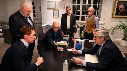 Junto al secreatrio general de la presidencia, Julio Vitobello, González García y Salvarezza, Fernández les muestra el kit a Rodríguez Larreta y Santilli