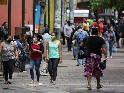 Mujeres con tapabocas caminan en la Calle Peatonal de Tegucigalpa (EFE)