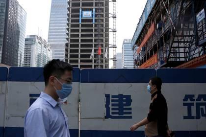 Dos personas caminan con barbijo en Beijing, en pleno brote de coronavirus (Reuters/ Tingshu Wang)