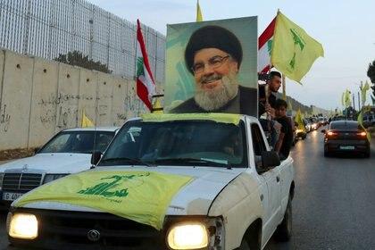 Los partidarios del líder de Hezbollah del Líbano, Sayyed Hassan Nasrallah, viajan en un vehículo decorado con banderas de Hezbollah y del Líbano y una foto suya, como parte de un convoy en el pueblo sureño de Kfar Kila, Líbano, el 25 de octubre de 2019. (Reuters)