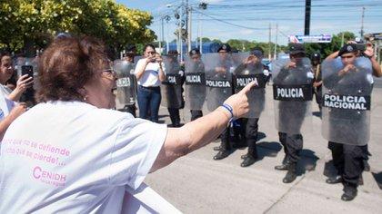 La doctora Vilma Núñez, presidenta del Centro Nicaragüense de Derechos Humanos (CENIDH) encara a policías que reprimen una actividad opositora.  (Foto cortesía La Prensa)